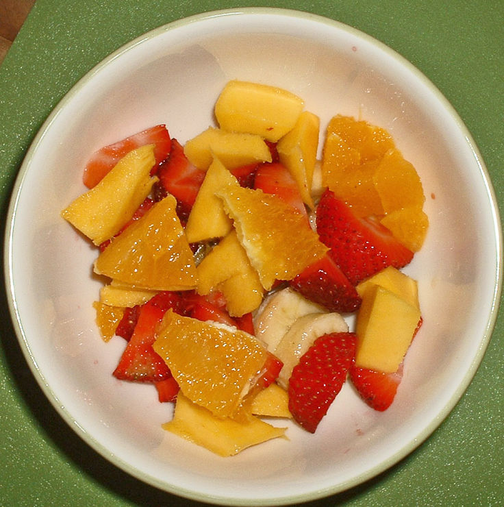 Ambrosia fruit salad is marinated to blend the flavors of a variety of fruits, topped with coconut and whipped cream