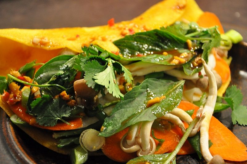 bahn xeo pancakes are usually served with fresh herbs, bean sprouts, Asian salad greens and a delightful homemade sauce.
