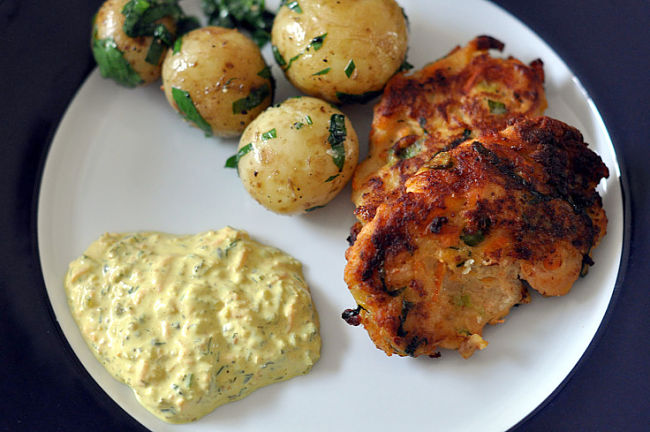 Fish cakes served with potatoes and a salad side serve