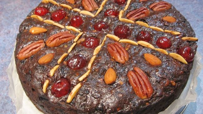 Rich fruit cake decorated with nuts and cherries