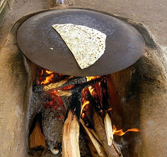 Traditional method of cooking Gozleme on a metal plate over and open fire which adds to the taste