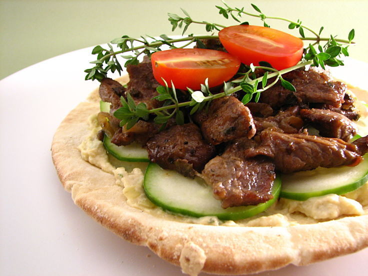 Pita topped with hummus lamb and salad