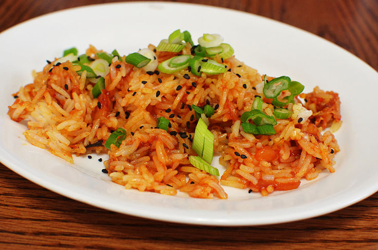 Adding toasted sesame seeds, fresh herbs, sliced chilli and other garnishes adds flavor to homemade Kimchi fried rice