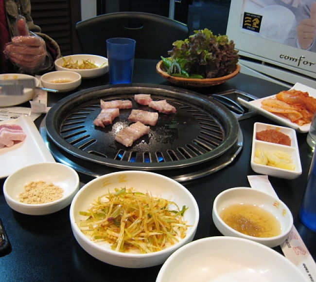 Gas burner style Korean barbecue cooker. You can do this at home with 'Baby' barbecues or camping units. See how in this article