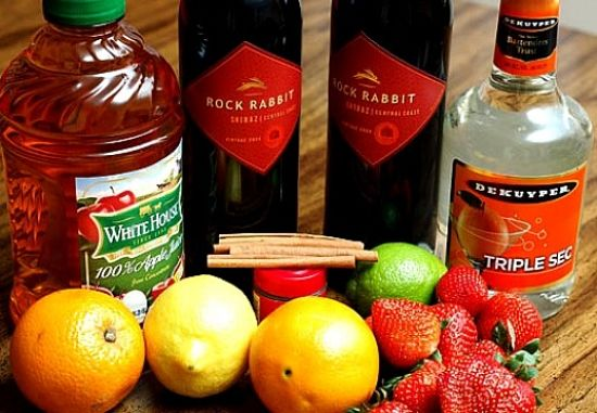 Ingredients for making wine and liqueur based Sangria with oranges, strawberry lime and spices. Delicious and so refreshing.