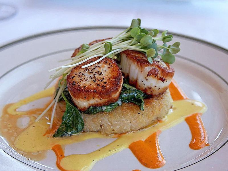 Seared sea scallops is a delightful and delicate dish that goes well with spinach and herbs, and a delicate wine sauce